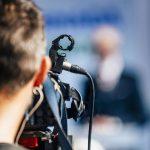 Press Conference Event. Cameraman Recording Male Speaker